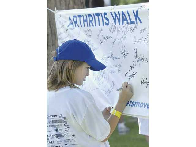 Caleb Arthorp, 12, signs the Arthritis Walk Wall of Heroes banner as he prepares to start the Arthritis Walk at Six Flags Magic Mountain on Sunday.