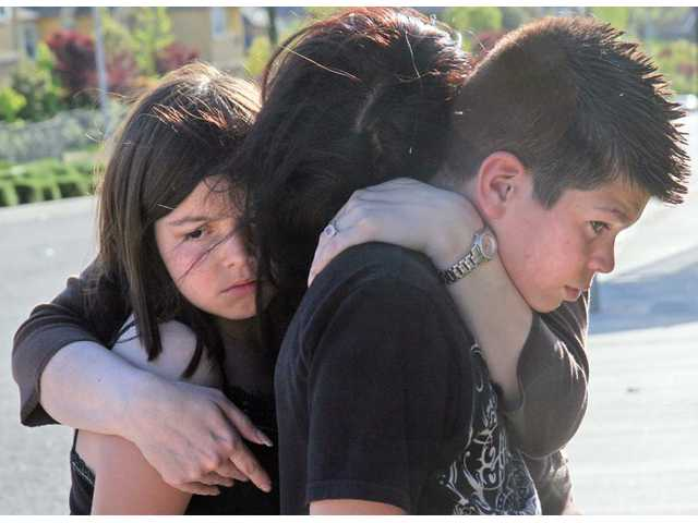 Jessica Laird hugs her children Janessa, 9, and Jonathon, 13, as they stand near the intersection of Plum Canyon Road and Santa Catarina Road, the location where her husband and father Jeff Laird was killed in a collision Saturday.