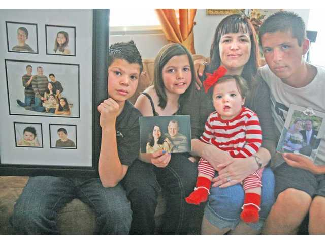 From left to right, Jonathon, Janessa, Jessica, Julyssa, and Yobany, 15, sit in their Saugus home with pictures of Jeff Laird. Laird was on his way to pick up his family to attend church when he and Garrett Brixon collided, just a block away from home.