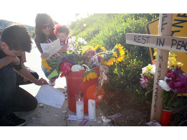 Jonathon Laird, 13, holds back tears his as mom Jessica Laird, holding 9-month-old Julyssa, reads letters left at her husband Jeffrey Laird's memorial near the corner of Plum Canyon Road and Santa Catarina Road on Monday afternoon. Laird was killed in a collision on Saturday evening, just one block away from his home.