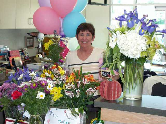 Cheryl Phillips poses with flowers brought to her by students at Peachland Avenue Elementary School. Phillips retired after 17 years as the school's library media tech on Thursday. Students and teachers say she will be missed and remembered most for always recommending good books.