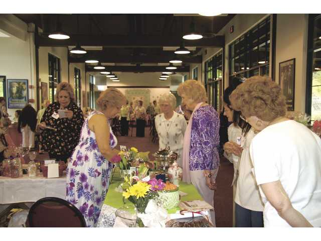 Attendees of the Heritage Reflections luncheon on April 23 browse the white elephant sale table. Members were asked to donate items to sell at the event. They also made gift baskets to auction off. The Questers chapter hosted the annual fundraiser to raise money for Hart Museum and Heritage Junction.