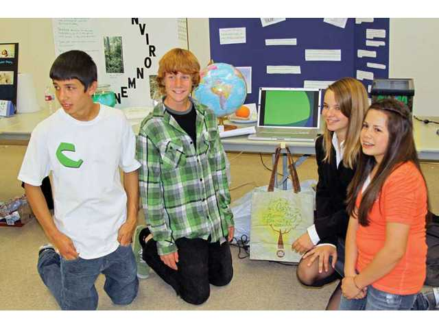 "Arroyo Seco Junior High School students Ray Orrick, Colin Maher, Aimey Beer and Brittney Guzman display their presentation about the environment during the school's ""Going Green"" symposium."