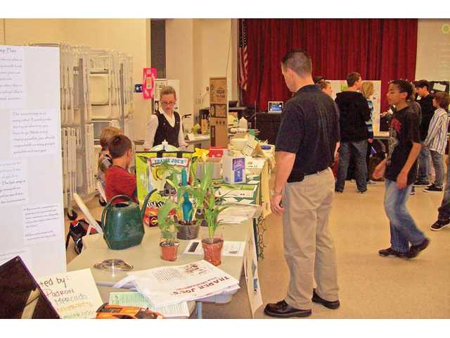 Students display exhibits about various green activities at the symposium.