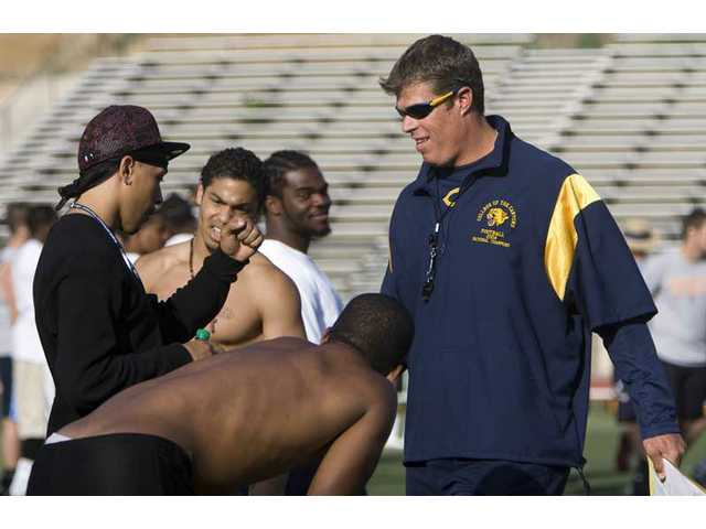 College of the Canyons head coach Garett Tujague, right, talks with his players during spring football practice at Cougar Stadium. Though successful in 2008, the Cougars' 12-1 season left the team and the head coach dissatisfied. In 2009, COC will have a different look, but is prepared to continue its winning tradition.