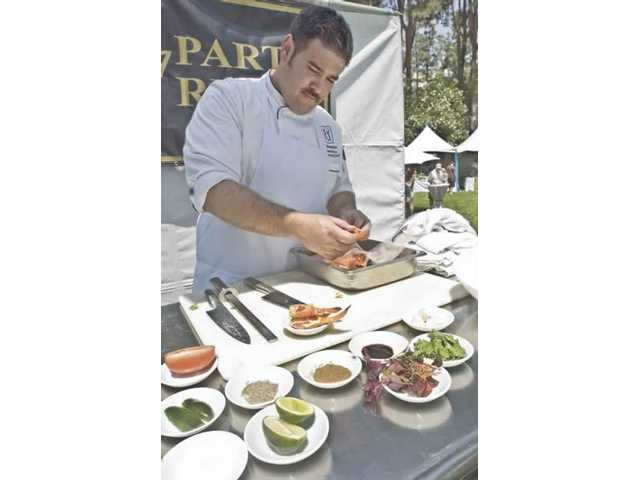Daniel Otto, an executive chef with The Oaks Grille, demonstrates the preparation of lobster gazpacho for onlookers.
