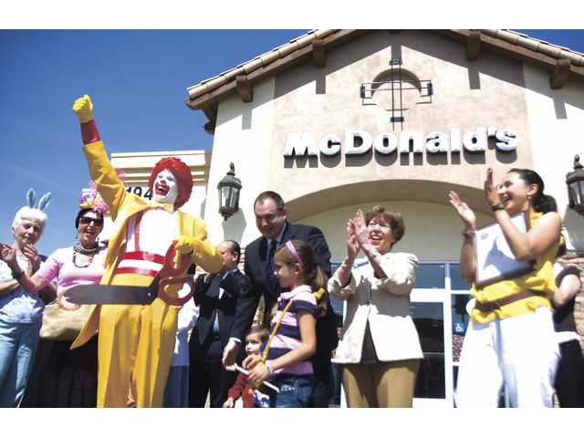 Ronald McDonald and others cheer after the ribbon-cutting ceremony of the new fast food restaurant opening at the Plaza at Golden Valley on Monday morning.