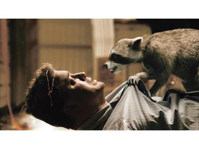 "Brendan Fraser and a ""costar"" are shown in a scene from ""Furry Vengeance."" The raccoon leads habitat-threatened animals in a rebellion against the construction of a housing development."