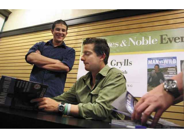 "The Discovery Channel's ""Man Vs Wild"" host Bear Grylls signs Ryan Pourroy's book during the book signing event at the Valencia Barnes and Nobles on Tuesday night."