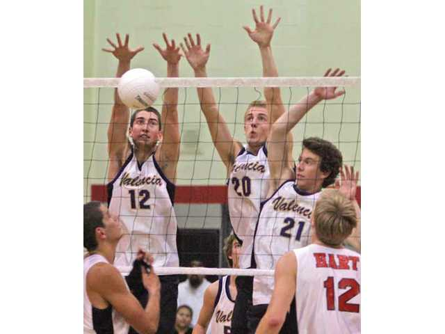 Valencia's Steven Crane (12), Griffin Nichols (20) and Broc Oppler (21) make a block on Thursday as Hart's Taylor Gregory, bottom left, and Tim Jenkins look on during the Vikings' 3-0 win. With the victory, Valencia won its eighth straight league title.