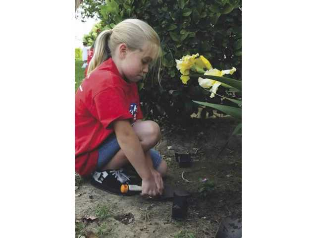 Abby Morris, 9, packs down dirt after planting a flower at Medows Elementary School in Valencia  with Junior Girl Scout Troop 368. The flower-planting was part of Pride Week.