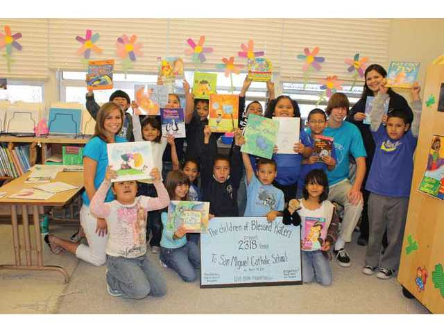 Allyson Weber, left, and Daniel Salovich, right, of the Give Books Foundation, Inc., stand with Principal Maryann Reynoso and first-graders at San Miguel Catholic School in Los Angeles as they hold up their new books. San Miguel students received more than 2,300 gently used books donated by children in the Blessed Kateri Religious Education program in April, which was a team effort by Blessed Kateri's parish.