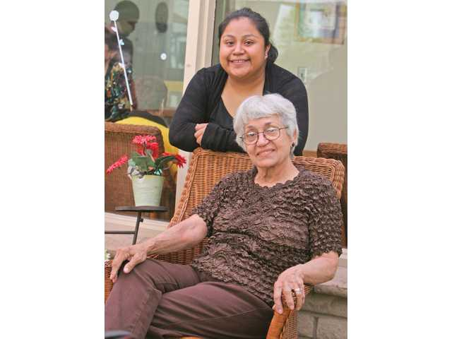 Jeny Vazquez, standing, 27, of Newhall, is a single mother of a 4-year-old girl. Seated is 75-year-old Iris Suarez-Villamil, mother to three sons and a grandmother of one granddaughter.