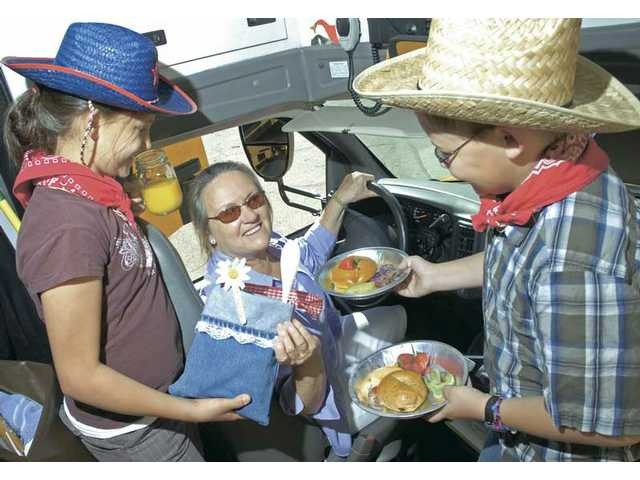 Live Oak Elementary student council presidents, Brooke Rapko, 11, left, and Ben Goosen, 11, serve a continental breakfast and present a gift bag made out of donated jeans to bus driver Cynthia Lewis in appreciation for her service to the Castaic students throughout the year.