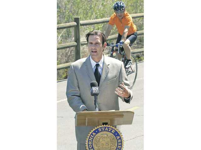 A bike rider uses the bike path near the Santa Clara River on Friday as Assemblyman Cameron Smyth describes his bill AB 1464, which promotes cycling in the Santa Clarita Valley.