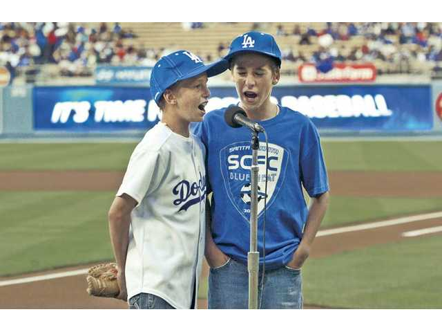 "Shaffery twins Mick, left, and Niall, 12, of Santa Clarita, announce ""It's time for Dodger baseball"" over the loud speaker at Dodger Stadium."