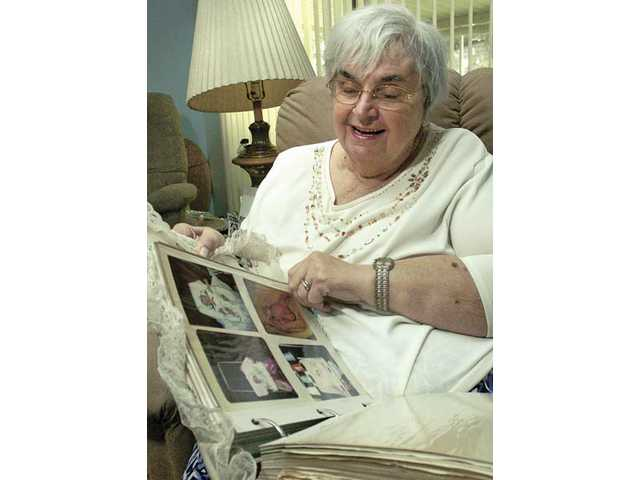 Carolyn Sears flips through her scrapbook of photos of the almost 80 children she has fostered over the years at her new home in Newhall on Wednesday.