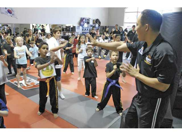 Fifth degree black belt Tae Kwon Lee, right,  leads a group of children in basic self-defense moves as part of the Kidz 'n Power safety workshop at ATA Martial Arts in Stevenson Ranch on Saturday.
