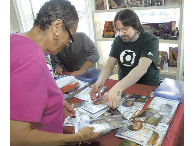 "Pamela Dilworth, left, gets her 32 copies of ""Female Force: Michelle Obama"" signed by the author Neal Bailey at the Brave New World comic store on Saturday."