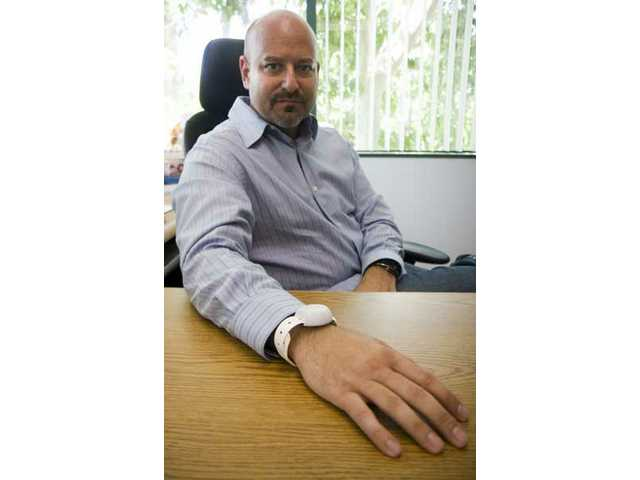 Kevin Tonoian, Technology Services Manager, wears the Project Lifesaver, a bracelet designed for special needs kids and the elderly population.