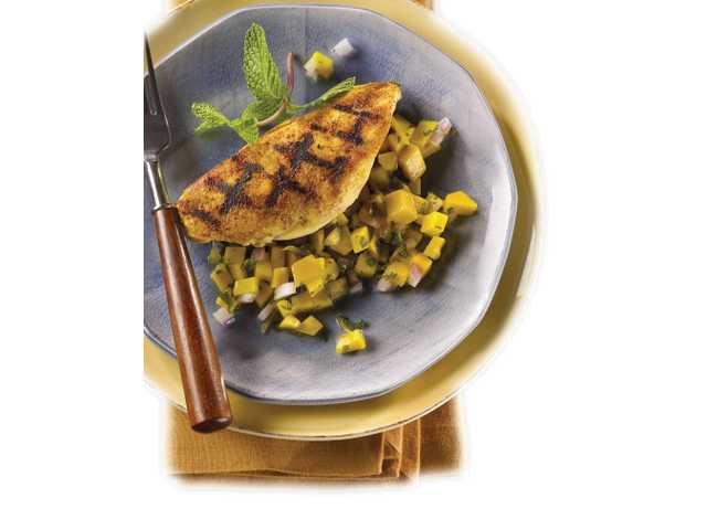 FRESHGrill pan chicken with fiery mango-ginger salsa Yield: Four servingsServing size: 1 chicken breast and 1/4 cup salsa1 tablespoon canola oil1 teaspoon curry powder1 teaspoon sugar1/2 teaspoon coarsely ground black pepper1/4 teaspoon salt4 boneless, skinless chicken breast halves (4 ounces each), rinsed, patted dry and flattened to 1/2-inch thicknessCanola oil cooking spray1 lemon, cut into quartersSalsa1 cup finely chopped mango2 to 3 tablespoons chopped fresh mint leaves1 teaspoon grated fresh ginger 2 tablespoons finely chopped red onion1/2 teaspoon lemon zest1 tablespoon fresh lemon juice1 teaspoon canola oil1. Combine 1 tablespoon canola oil, curry powder, sugar, pepper and salt. Brush over chicken and let marinate for 15 minutes. 2. Meanwhile, stir together salsa ingredients in a small bowl. 3. Coat a grill pan with canola oil cooking spray and place over medium-high heat until hot. Add chicken, discarding any marinade. Cook chicken four minutes on each side, or until no longer pink inside and juices run clear. Transfer to a serving platter. Squeeze lemon juice over chicken; serve with salsa.Exchanges: 1 fruit, 3 lean meat, 1/2 fatNutritional information (per serving): 205 calories, 65 calories from fat, 7 g total fat, 1.1 g saturated fat, 65 mg cholesterol, 175 mg sodium, 11 g total carbohydrate, 1 g dietary fiber, 9 g sugars, 25 g protein