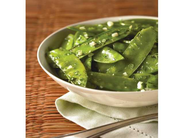 FASTGarlic snow peas with cilantroYield: Six servingsServing size: 1/2 cup3 teaspoons canola oil, divided3 cups fresh (or frozen and thawed) snow peas, patted dry and trimmed4 medium cloves garlic, minced1/4 teaspoon salt 1/4 to 1/2 cup chopped fresh cilantro leaves1. Working in two batches, heat 1 1/2 teaspoons of canola oil in a large nonstick skillet over medium-high heat. Add half of the snow peas; cook three minutes or until just beginning to brown on edges, using two utensils to toss easily. Add half of garlic and cook 30 seconds, stirring constantly. Set aside on a separate plate.2. Repeat with remaining 1 1/2 teaspoons of canola oil, snow peas, and garlic. When cooked, return the reserved snow peas to skillet; add salt and cilantro, and toss gently, yet thoroughly. Serve immediately for peak flavors. Exchanges: 1 vegetable, 1/2 fatNutritional information (per serving): 45 calories, 20 calories from fat, 2.5 g total fat, 0.2 g saturated fat, 0 mg cholesterol, 100 mg sodium, 4 g total carbohydrate, 2 g dietary fiber, 2 g sugars, 2 g protein