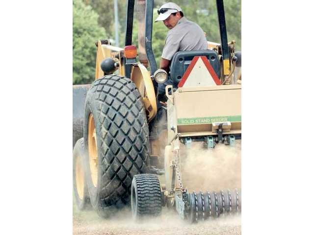 City of Santa Clarita groundskeeper Alfredo Moraca drives a backhoe with an automated seeding machine through Central Park in Saugus on Monday.
