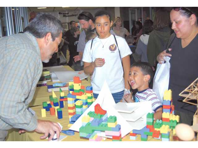 A young guest at the Discovering Careers Expo watches as a College of the Canyons professor performs an architectural demonstration with Lego blocks.