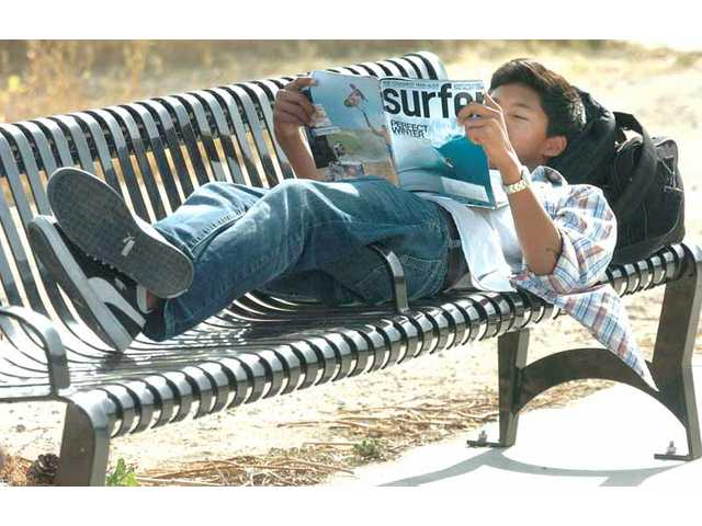 Valencia High School freshman Calvin Olbes, 14, enjoys the sun on Wednesday afternoon while reading through a copy of Surfer magazine, as he waits for the bus at the corner of Decoro Drive and Dickason Drive in Valencia. The Santa Clarita Valley is in for a warm and sunny weekend, according to the National Weather Service. Temperatures are set to hover around 80 degrees through Wednesday, with nighttime lows to be in the mid-50s.