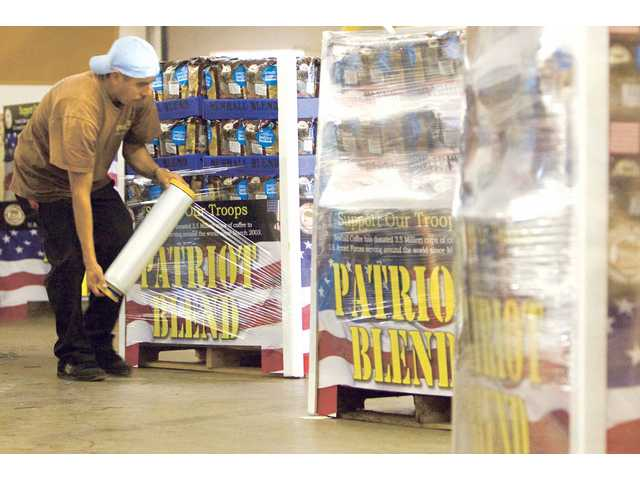 Angel Martinez wraps plastic on a palette containing 400 bags of Newhall Coffee Roasting Company being delivered to numerous Southern California Sam's Club stores.