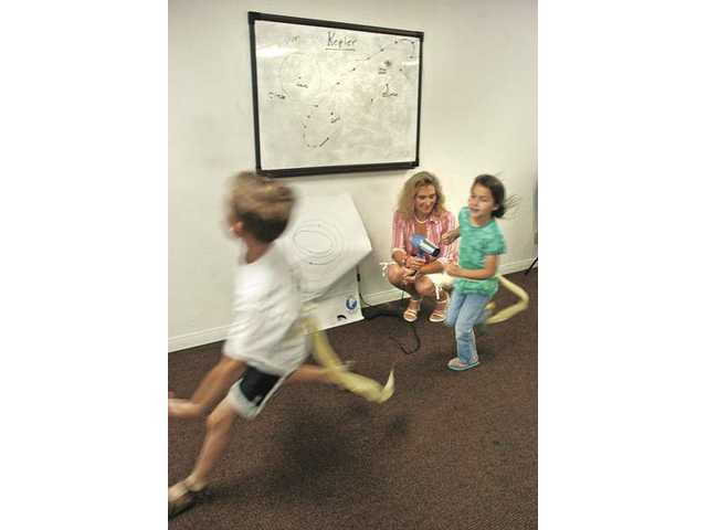 Blake Kirshner, 8, left, and Caroline Carreon, 6, run past instructor Elizabeth Johnson as she demonstrates how solar winds effect the tails of comets at Huckleberry Learning Center at Newhall Church of the Nazarene.