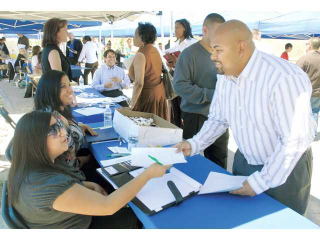 Jose Luis Aparicio, right, hands in a job appliction to Amber Isaguirre,  Marketing team-mate from Sam's Club at the College of the Canyons,  Canyon Country Campus Job Fair on Wednesday.