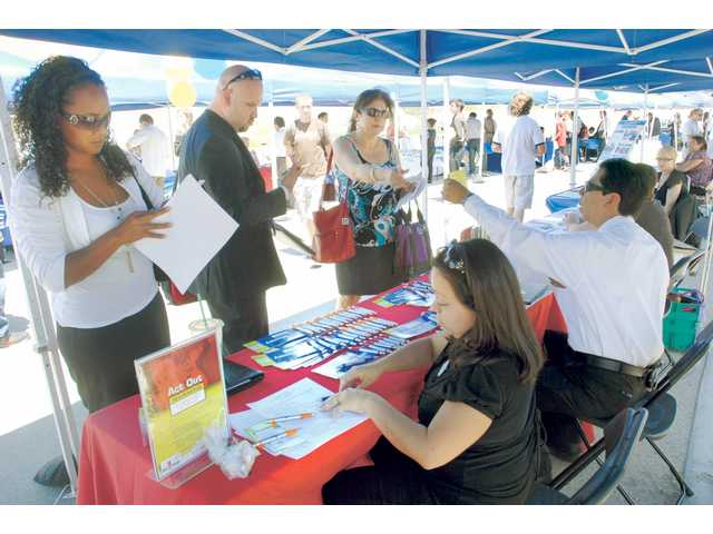Adreena Thomas, left, joins hundreds of other job fair attendees as she gets a job application from Andrea Wynn, seated,  of the Six Flags Magic Mountain HR dept. at the College of the Canyons, Canyon Country Campus Job Fair on Wednesday.