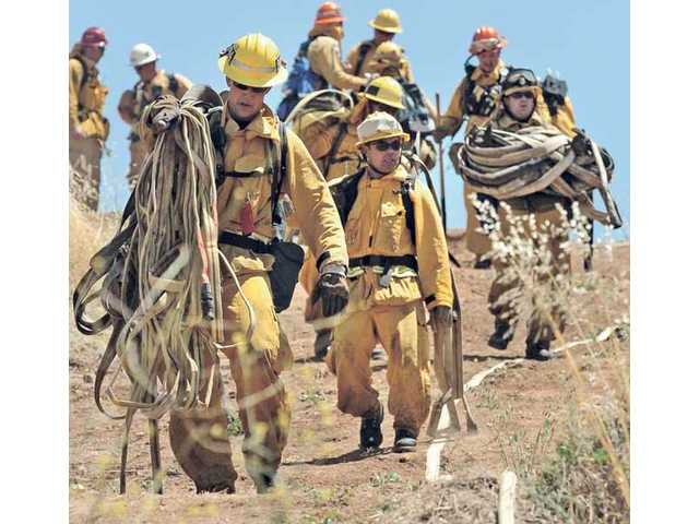 Los Angeles County firefighters carry their hoses and equipment down the hill after participating in their 2010 training on fighting brush fires at Pitchess Detention Center on Thursday.