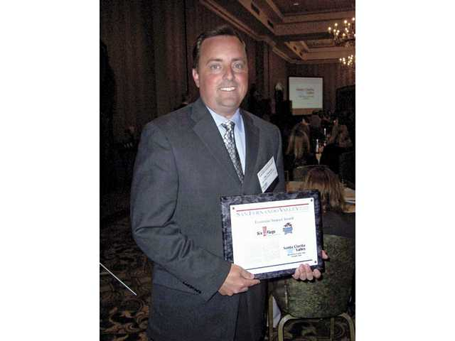 Jay Thomas of Six Flags Magic Mountain holds the award the theme park won for Biggest Economic Impact.