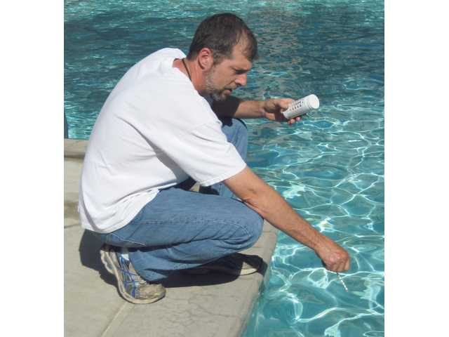 Ben Honadel, of Pools by Ben, tests the chemicals in pool water with a small test strip.