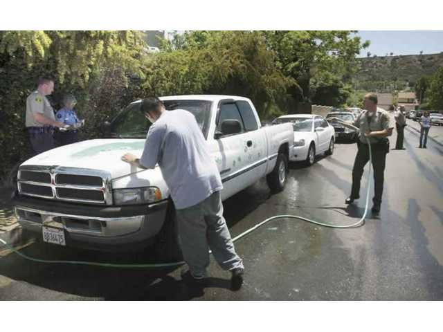 Los Angeles County sheriffs deputies take fingerprints and help out Saugus High junior David Gandra wash off the graffiti painted onto Gandra's white truck parked on a side street near Saugus High School on Wednesday.