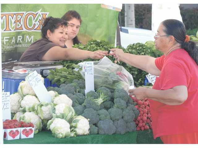 Ramona Thomas, right, of Castaic buys vegetables from Irma, left, and Silvia Suarez of Azteca Farm at the Farmers' Market held at the Castaic Sports Complex on Saturday.