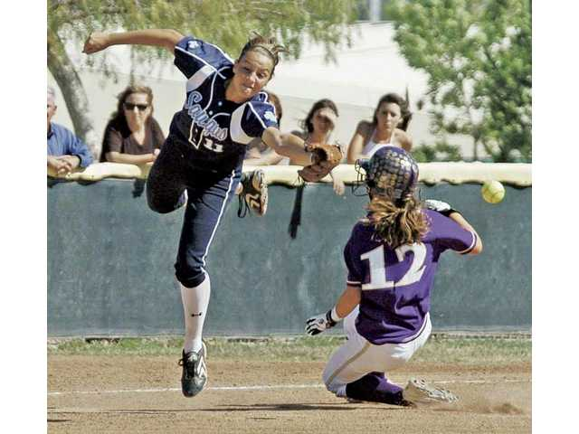 Saugus' Jenna Kelly (11) reaches for a throw as Valencia's Megan Foglesong slides into third base Thursday at Valencia High. Valencia won 7-2.