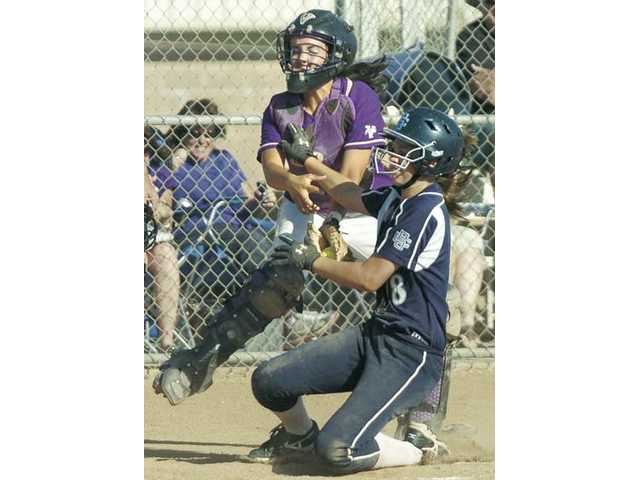Valencia catcher Amy Moore, left, absorbs a collision with Saugus' Karlee Bickford and makes a tag Thursday at Valencia High. The Vikings won the game 7-2 and with the victory claimed a share of the Foothill League title.