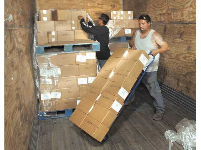 Armando Gaindo, right, wheels out some of the three tons of Rachael Ray dog treats that were donated to the Villalobos Rescue Center.