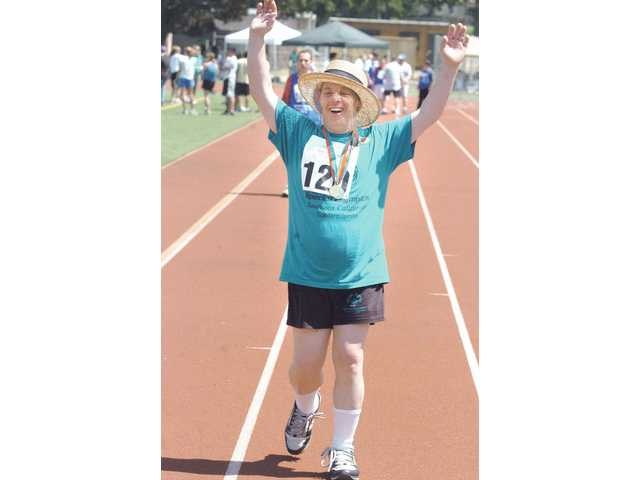 Santa Clarita Special Olympics athlete John Lever heads for the finish line  in the 100-meter walk event at  Hart High on Saturday.