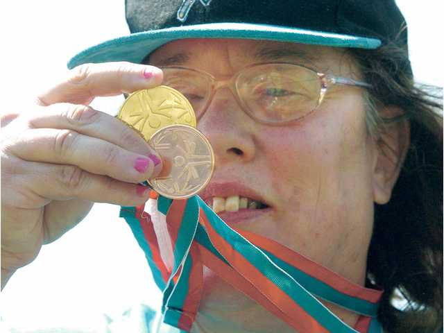 Susan Treister, a member of the Santa Clarita Valley team of athletes, known as The Sharks,  looks at her medals from the Special Olympics.