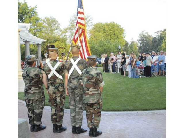 The SCV Young Marines Color Guard presents the flag as about 100 attendees say the Pledge of Allegiance at the Armed Forces Day Candlelight Vigil at Veterans' Historical Park on Saturday night to honor those serving and those who have served.