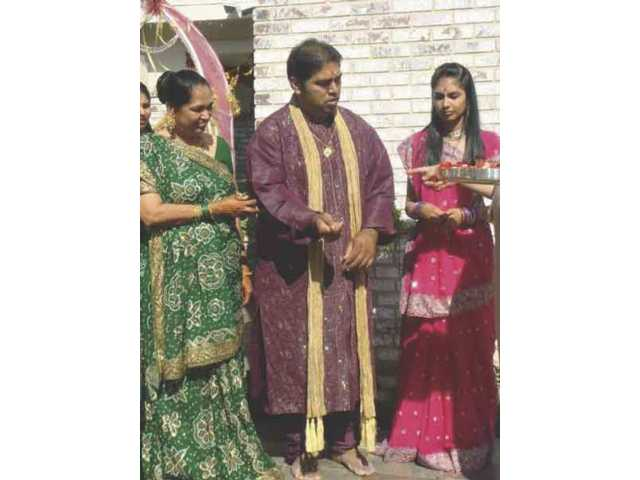 During the first day of the wedding week, the bride's family performs a ceremony at their house to place a small pillar in their front yard. The pillar represents the foundation of the wedding canopy, where the bride and groom will perform the wedding ceremony a few days later. Here the ceremony is led by Parimal Rohit (center), his sister, Mona (right), and their mother, Bharati (left).