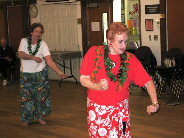 "Polynesian dance instructor Winona Plantenberg, right, shows Dolores Fox how to ""fish"" during a hula at the Santa Clarita Valley Senior Center on May 5."
