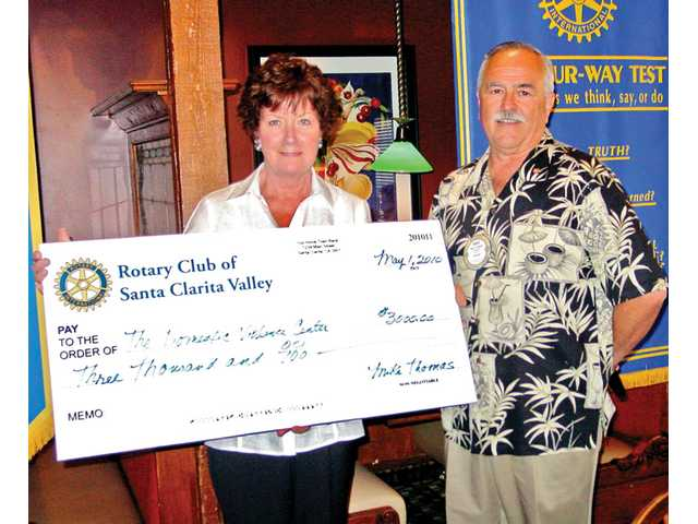 Mary Rees, president of the board for the Domestic Violence Center of SCV,  receives a check for $3,000 from Rotary President Mike Thomas.