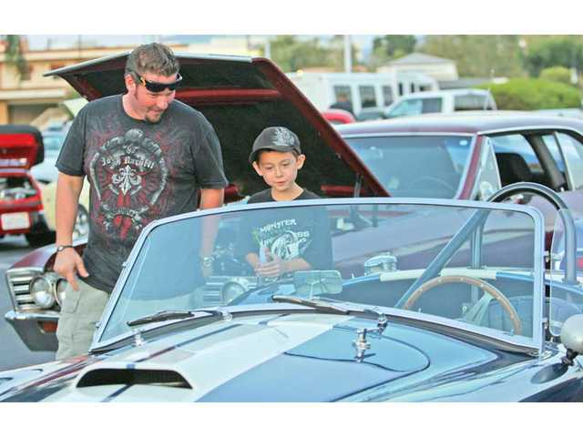 "Cesar Ranuschio, of Canyon Country, and Kaleo Inez, 9, of Valencia, check out a classic car Wednesday at ""Cruise Lyons Avenue"" in Newhall."