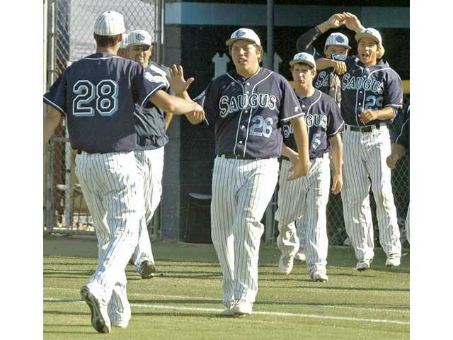 Saugus pitcher Kyle Hooper (28) is greeted by teammate Tommy Kister (26) after the last out Tuesday in the wild card of the CIF-SS Division I playoffs.