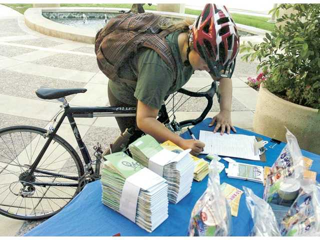 Santa Clarita City Hall employee Kelly Minniti joins 50 other bike riders by signing the check-in sheet at the Bike to Work Day bicycle pit stop at City Hall.